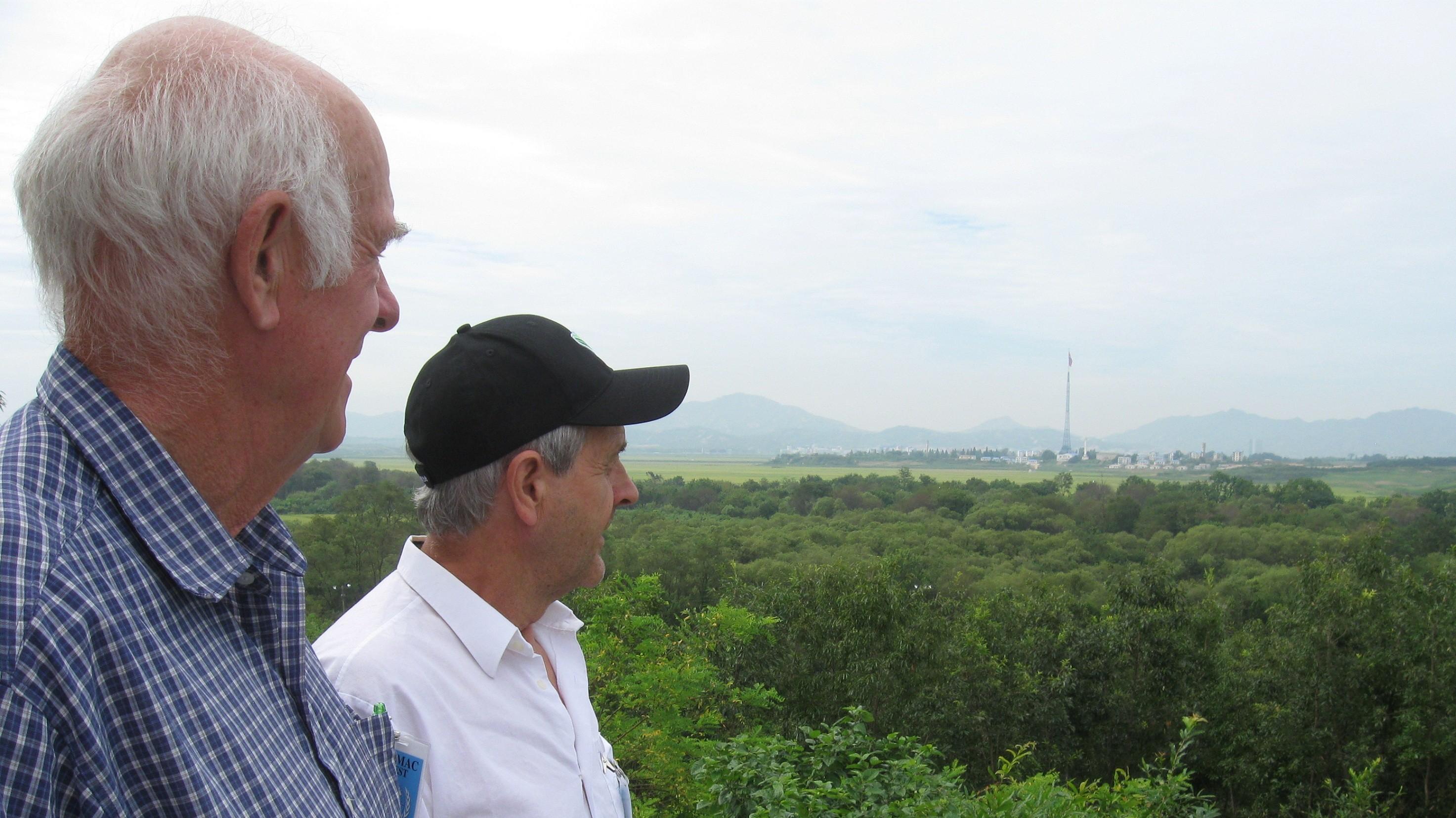 Anders Nyquist (t v) och Åke Mård blickar ut över Kijong-dong - den nordkoreanska staden som inte finns. Foto: Per-Erik Persson