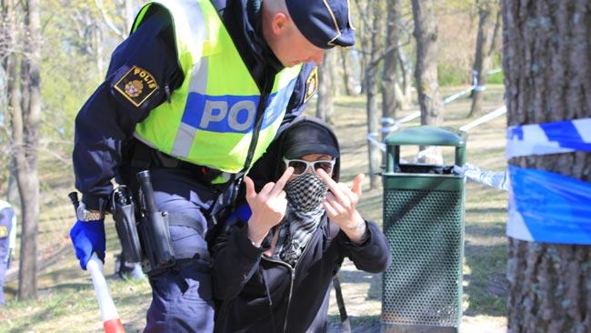 Maskerad kille blir av med vuvuzela som polisen håller i handen och får en tilrättavisning - Foto: Nyheter Idag