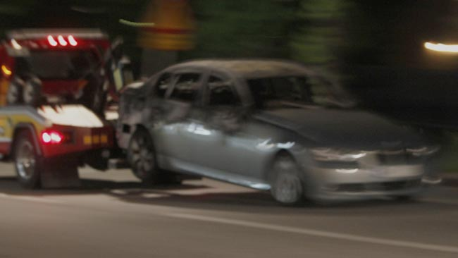 En bärgningsbil transporterar en utbränd BMW i Husby, natten mot måndagen. Foto: Nyheter Idag