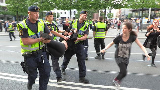 Polisen bär bort en  motdemonstrant i Stockholm i samband med Åkessons tal inför EU-valet. Foto: Nyheter Idag
