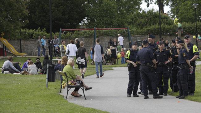 Här ser vi polisen hålla koll i närheten av tårtkvinnan med sällskap. Foto: Nyheter Idag