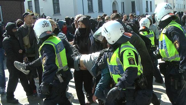 Motdemonstrant bärs iväg av polis. Foto: Fritz Schibli / TOPNEWS.se