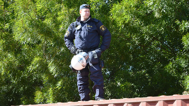 Här ser vi en polis stå på en container för att överblicka situationen. Foto: Fritz Schibli / TOPNEWS.se