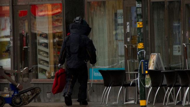 En polis med kraftiga skyddskläder närmar sig lokalen. Foto: Chang Frick / Nyheter Idag