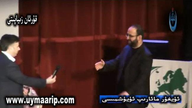 Här står Mehmet Kaplan bredvid Milli Görüs grönvita symbol. Foto: Faksimil Youtube