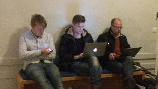 Här sitter tre journalister på en bänk utanför möteslokalen i Alvik. Foto: Sven Pernils