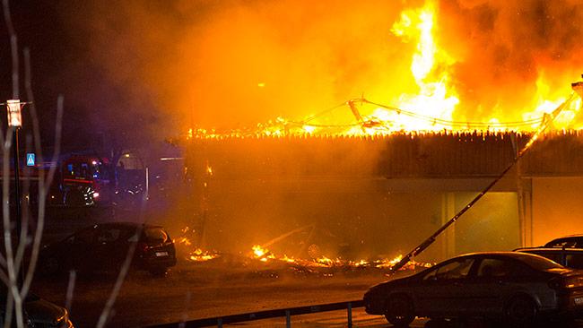 Här brinner ett helt parkeringsgarage ned till grunden. Foto: Chang Frick / Nyheter Idag