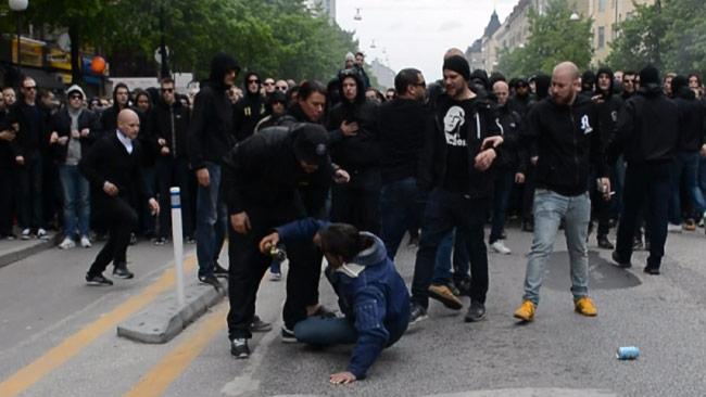 En man låg ner och fick ta emot sparkar från supportrarna. Foto: Nyheter Idag