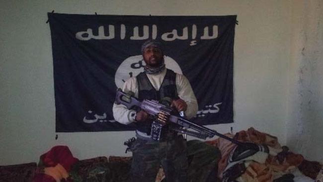 Al Amin Sultan poserar framför en islamistflagga. Foto: Polisen