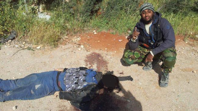 Al Amin Sultan poserar vid liket av en av de mördade männen. Foto: Polisen