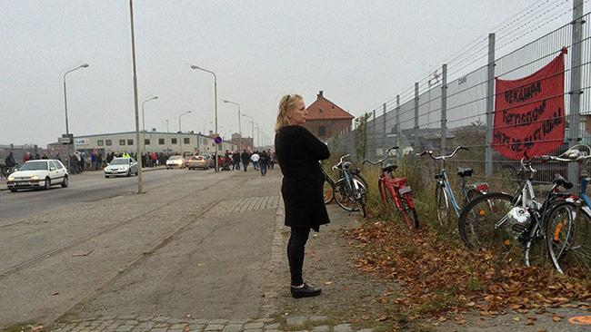 En kvinna tittar på en banderoll om att bekämpa fattigdom utanför tiggarlägret i Malmö. Foto: Privat