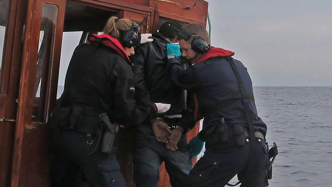 Här griper svenskarna den misstänkte människosmugglaren på bar gärning. Foto: Kustbevakningen