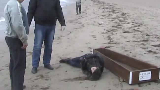 En död människa på stranden i Turkiet ska precis lastas i en kista. Foto: Faksimil Youtube