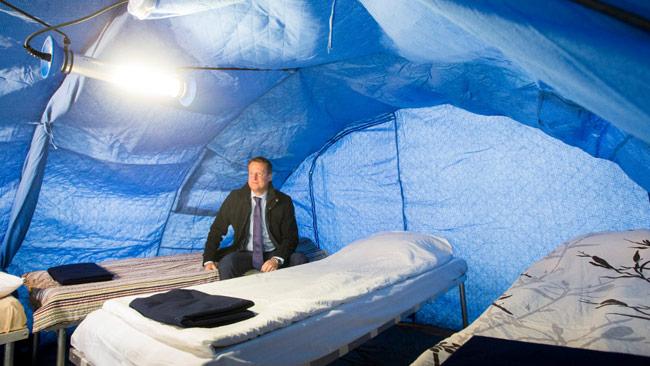 Inrikesminister Anders Ygeman sitter i ett tält. Foto: Johan Eklund/MSB