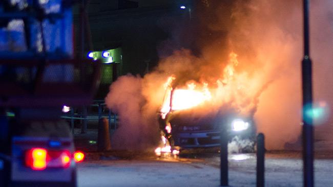 Här brinner bilen intill en stor byggnad i Norsborgs centrum. Foto: Nyheter Idag