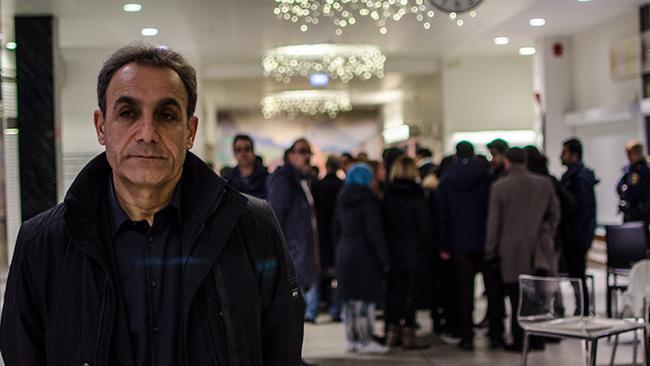 Rebwar Resid står vid huvudingången på Karolinska. I bakgrunden har hans kurdiska vänner samlats i avvaktan på besked om den skjutne mannen kommer överleva. Foto: Nyheter Idag