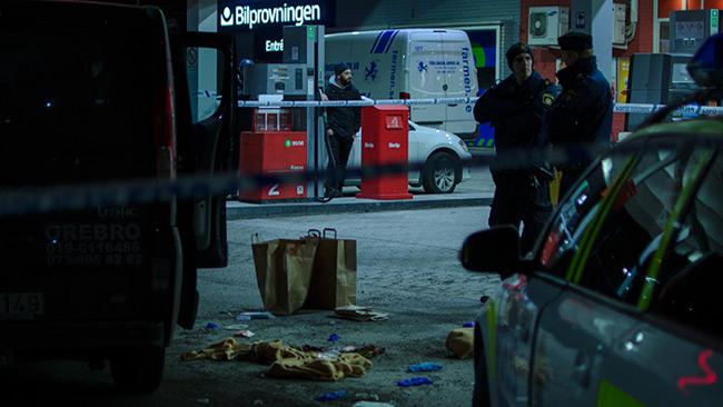 Två poliser håller vakt vid avspärrningen utanför bensinstationen. Foto: Nyheter Idag