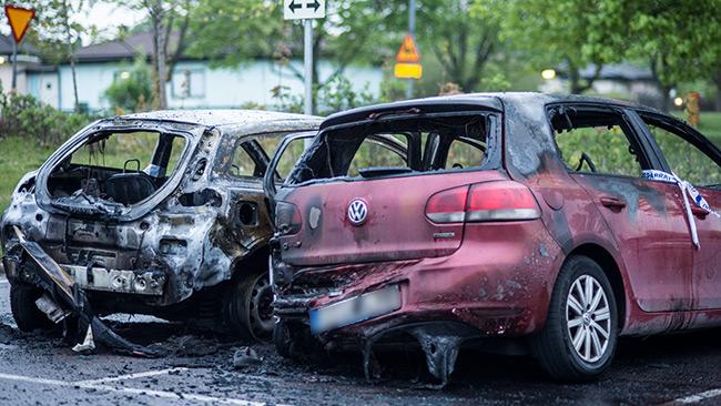 Två brandskadade bilar stod på tisdagsmorgonen på en parkering i ett villaområde i Fittja. Foto: Nyheter Idag