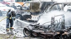 En brandman släcker bilar som brunnit i centrala Alby. Foto: Nyheter Idag
