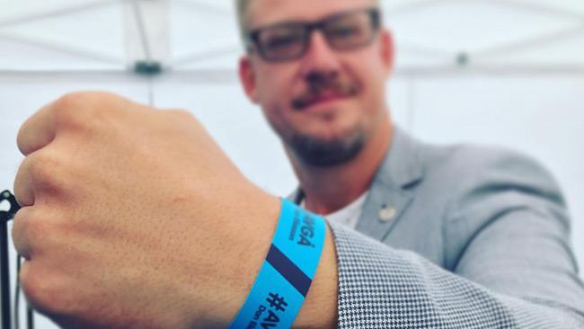 Linus Bylund (SD) poserar med armbandet som uppmanar till Eliassons avgång.