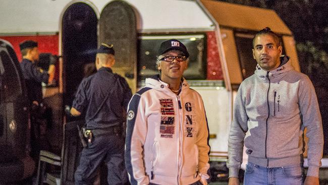 Raphael Nilsson (t.v). I bakgrunden poliser som undersöker en brandskadad husvagn. Foto: Nyheter Idag