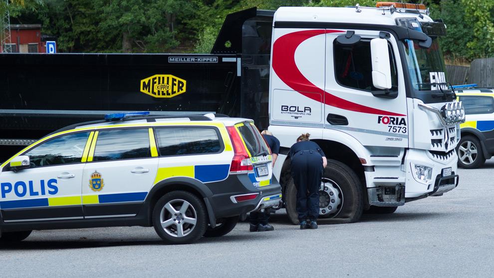 Polisen undersöker ett punkterat däck på lastbilen. Foto: Nyheter Idag