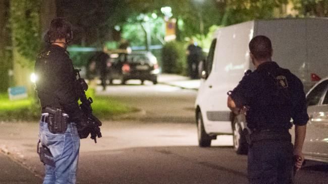 Tungt beväpnad polis står och bevakar innanför det avspärrade området. Foto: Nyheter Idag