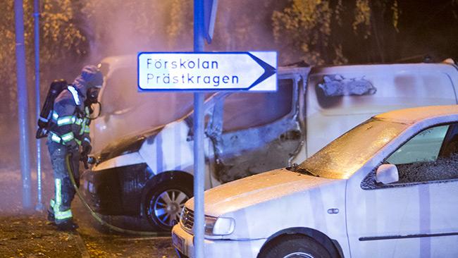 En brinnande bil släcks av räddningstjänsten vid ett dagis i Hallunda. Foto: Nyheter Idag