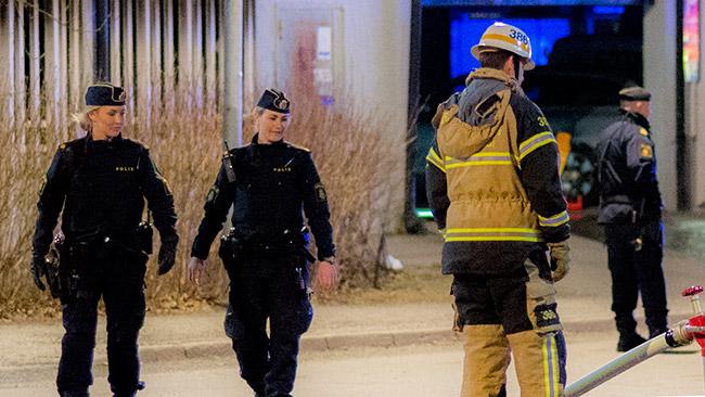 Två poliser spanar in brandmannens slang, på plats i Rågsved. Foto: Nyheter Idag