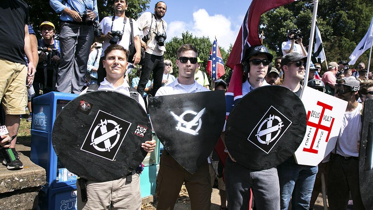 Demonstranterna bär sköldar dekorerade med fasces – fascismens symbol. Foto: Karla Cote