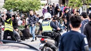 En polis på moped kör förbi de protesterande afghanerna. Foto: Nyheter Idag