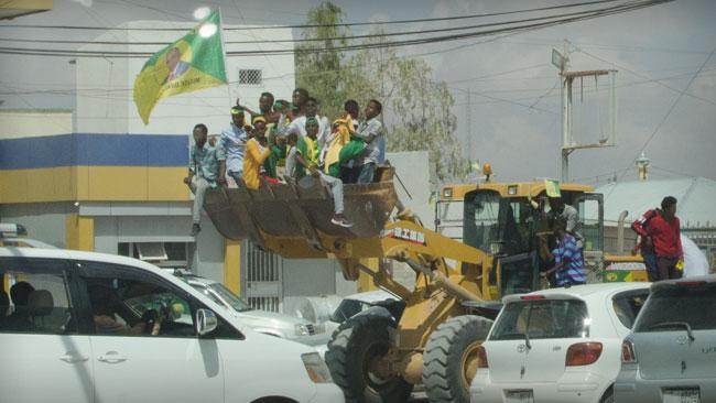 Kulmiye-sympatisörer åker runt, hoppandes, i en grävskopa i Hargeisa